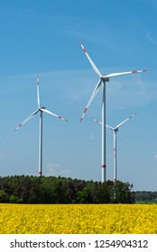 Wind energy plants and a field of blooming oilseed rape seen in Germany
