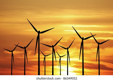 Wind energy turbines with a sunset sky