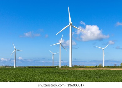 Wind engines in green field with corn and clouds