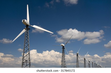 Wind farm against country landscape. Blue sky with clouds are in background.