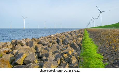 Wind farm along a dike in a lake in sunlight in spring