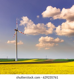 Wind farm with spinning wind turbines amidst agricultural land of rapeseed in dramatic light. Sustainable and renewable power production, ecology and environmental conservation concept.