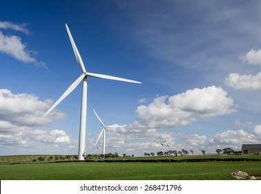 Wind Farm - Wind turbines in field with blue sky and clouds behind.