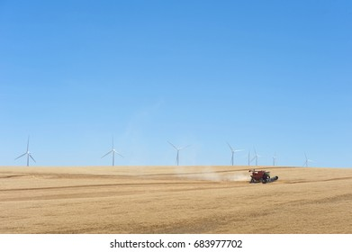 Wind farm and a wheat field with a combine harvester