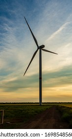 wind generator in grass field at sunset