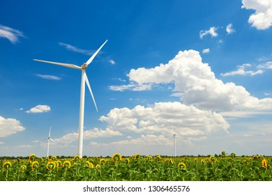 The wind generator in sunflower field. Beautiful landscape with bright cloudy sky. Eco energy concept.