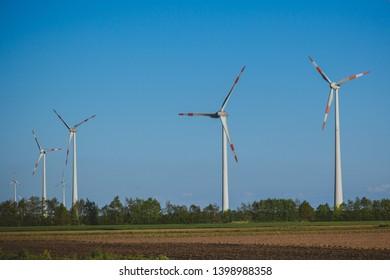 Wind generators in a field in Germany. Green energy in Europe. Wind turbines. Renewable energy sources.