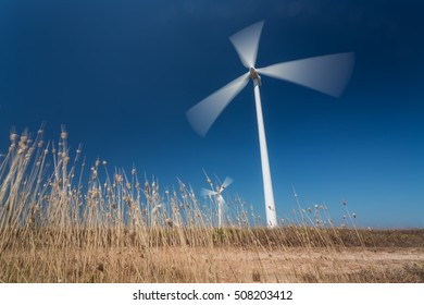 Wind generators in motion from below, grass in the foreground. Portugal.