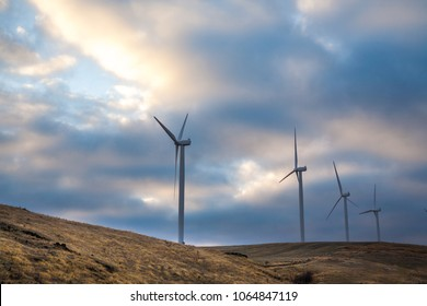 Wind generators in Sherman County Oregon wheat country are shown against a cloudy and blue sky.    Located a few miles south of the Columbia River Gorge.