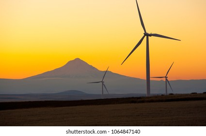 Wind generators in Sherman County Oregon are shown against an orange sunset sky.    Located a few miles south of the Columbia River Gorge.