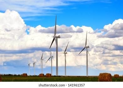 Wind generators standing in farmland under beautiful prairie skies.