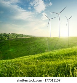 Wind generators turbines on sunset summer landscape