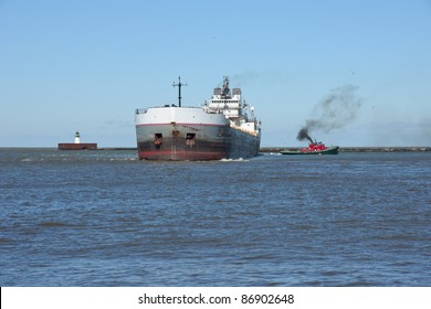 Wind gusts of 25 mph cause a single tug boat to struggle to control the stern of a Great Lakes bulk carrier ship inside the Lake Erie break wall at Cleveland, Ohio