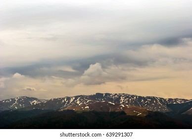 Wind matured clouds and snowy mountain peaks moody scene.