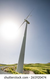 Wind mill  power turbine  generators against the sun  generating electricity from wind.  Concept of renewable energy sources.