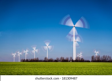 wind mills on a green meadow with blue sky representing sustainable and renewable energy