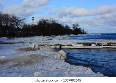 Wind Point Lighthouse in winter on a bright afternoon with the ice covered shoreline and pier in the foreground.