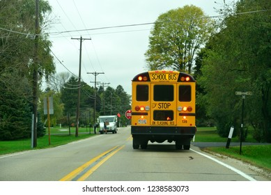 Wind Point, Wisconsin / USA - October 1, 2018: School bus stops traffic to allow children safely off the transport.