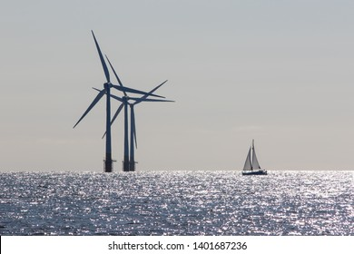 Wind power. Environmentally friendly sailing yacht. Offshore windfarm turbines. Tranquil scene of renewable resource power and travel with low carbon footprint lifestyle. Ecology landscape.