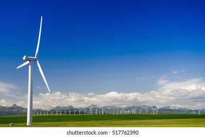 Wind power generation mill against a background of mountains and a wind farm.