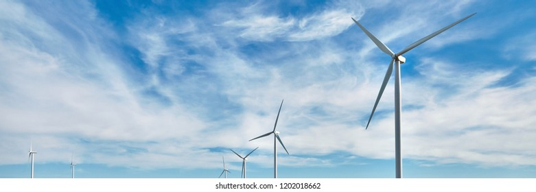 Wind power generator on blue sky background. Renewable energy source. Powerful and ecological energy concept