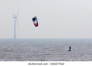 Wind power. Kitesurfer surfing by offshore windfarm turbine. Green energy represented by lone surfer on the sea on a misty morning using alternative wind energy.