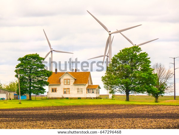 Wind power looms over farm house Midwest USA Illinois