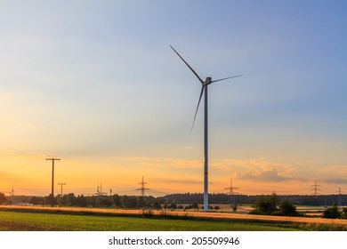 wind power plant in a field at sunset