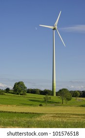Wind power plant - A wind turbine in rural idyllic landscape under  blue sky and moon.