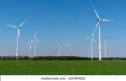 Wind power plants, green fields and blue skies seen in rural Germany