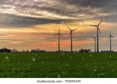 Wind power plants, sunset and first snowfall
