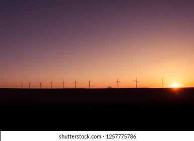 Wind power stations producing renewable energy in a beautiful sunset