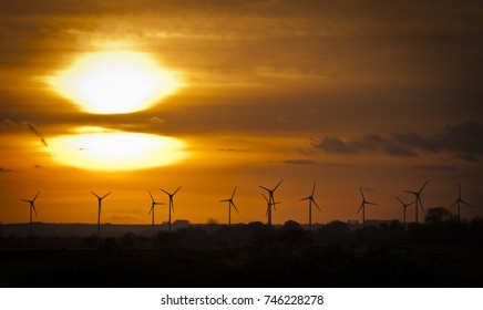 Wind Power Sunset, Renewable Energy, Climate Change. Silhouette of wind turbines on a yellow sunset.
