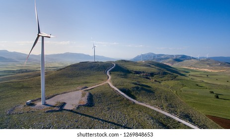 Wind power turbines generating electricity, Energy Production with clean. Green landscape and bird's eye aerial shot