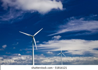 Wind power turbines on a blue and cloudy sky.