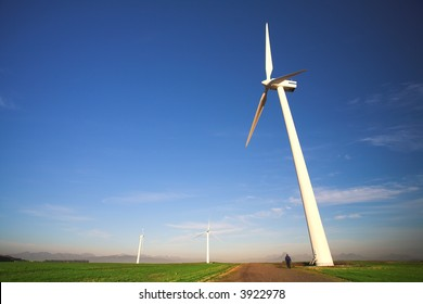 Wind powered electricity generator standing against the blue sky in a green field on the wind farm. A man is walking past the first generator