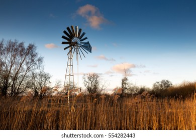 Wind pump with blue sky and farmland in background.