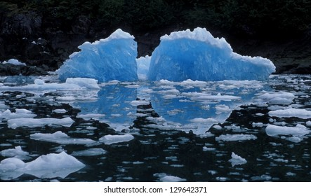 Wind, rain, sun and sea sculpt giant ice floes into dramatic ice sculptures. Only about one-ninth of the volume of an iceberg is above water. Le Conte Bay, Tongass National Forest Southeast Alaska.