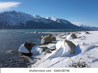 Wind sculted snow on the rocky beach near the Chilkat Inlet in Southeast Alaska with mountains in the distance on a sunny winter day.