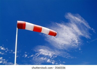 a wind sock and cloudy sky in the background
