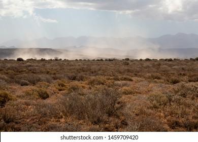 Wind swirls sand on dry prairie in Africa