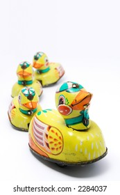 Wind up tin toy duck with three ducklings on white background. Narrow depth of field with duck in focus.