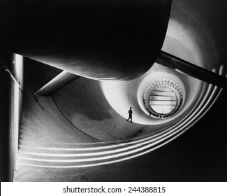 Wind tunnel at Langley Aeronautical Laboratory in the 1940s, to study the effects of air moving past solid objects. Photo by William P. Taub, NASA photographer, who is also pictured in the image.