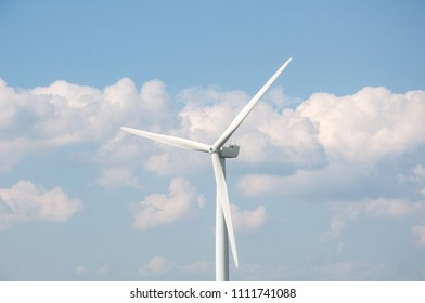 Wind turbine against blue sky and clouds background