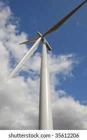 Wind turbine against blue sky with clouds