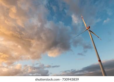 wind turbine against cloudy sunset sky
