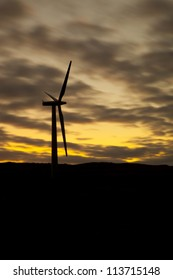 wind turbine against a sunset