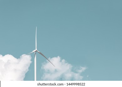 Wind turbine alone against sky with negative space.  Close up wind turbine against blue sky with idyllic white clouds, wind power concept with copy space. Technology in nature environment no people.