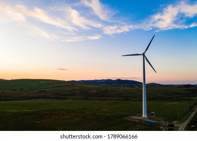 Wind turbine, alternative energy, wind energy, one windmill in a field in the mountains, top view of a wind turbine at sunset.