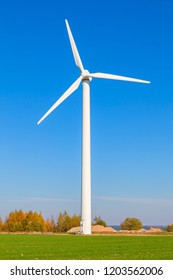 Wind turbine among a green field on a sunny autumn day